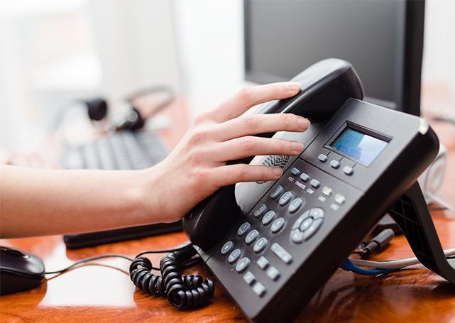 Pracownik biurowy odkłada słuchawkę telefoniczną